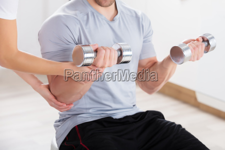 instructor helping man to exercise