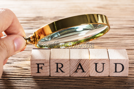 person placing magnifying glass over fraud