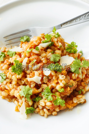 perlgerste und tomateneintopf auf weisser platte