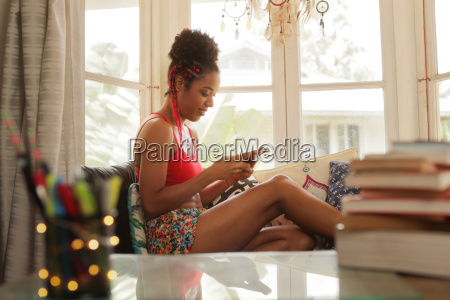 young black woman texting on phone
