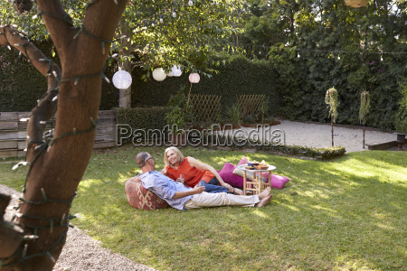 mature couple enjoying drinks in backyard