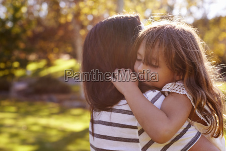 loving mother hugging daughter in park