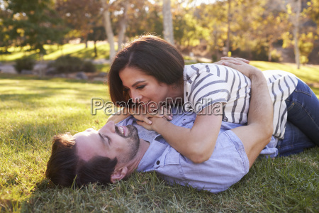 romantic couple lying on grass in