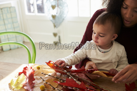 mother and daughter making autumn decoration