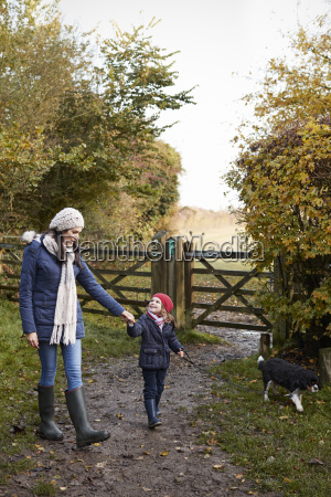 mother and daughter taking dog for