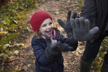 granddaughter wearing grandfathers gloves on autumn