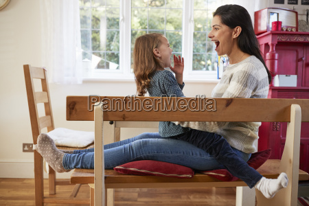 daughter sitting on mothers lap at