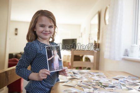 young girl looking at family photographs
