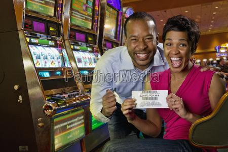 aufgeregtes paar zeigt spielgutschein im casino