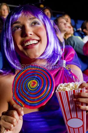 frau isst suessigkeiten und popcorn im