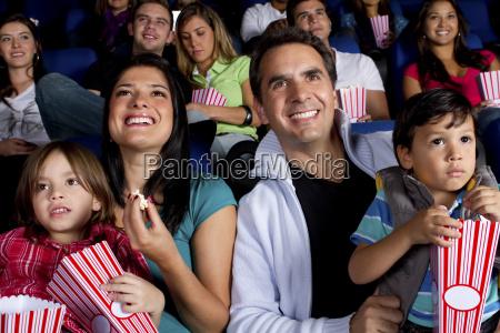 hispanische familie die popcorn im kino