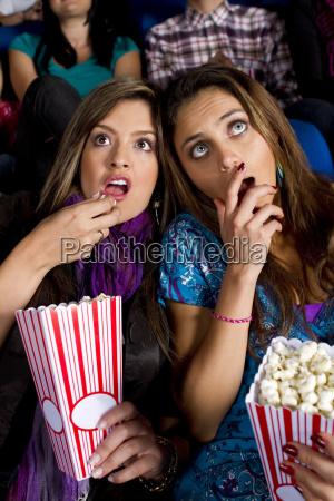 hispanische freunde geniessen popcorn im kino