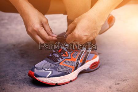 haende die schuhe zum joggen anbinden