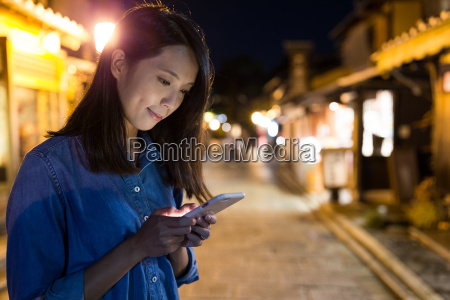 woman using cellphone in old town