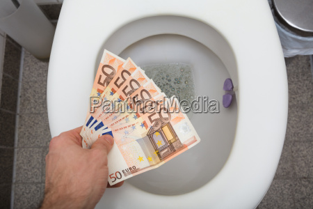 mans hand throwing fifty euro notes