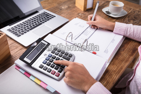 businesswoman calculating tax on desk