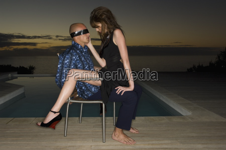 blindfolded man sitting on a chair