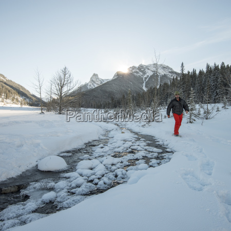 man schneeschuhe hinter schneebedeckten waldberge