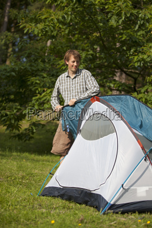 camper puts finishing touches on tent