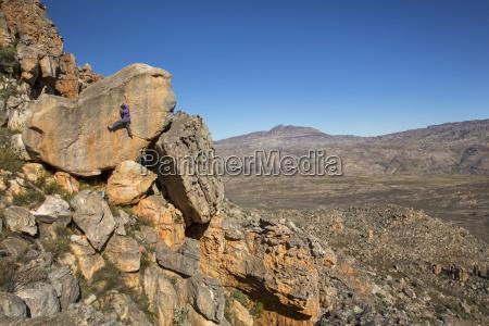 young man climbing boulder in natural