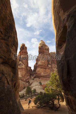 a woman walks between sandstone towers