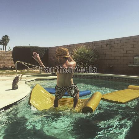 mann faellt vom floss ins schwimmbad