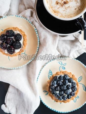 zwei beerenkuchen und ein cappuccino
