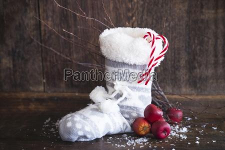 ein weihnachtsstiefel mit aepfeln und zuckerstangen