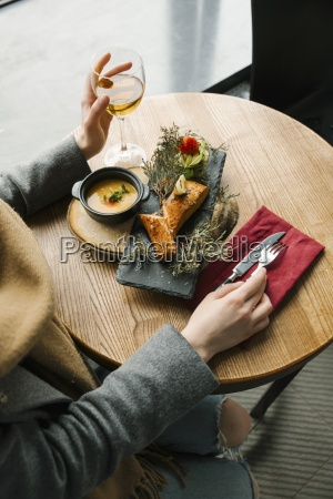 woman eating grilled salmon on juniper