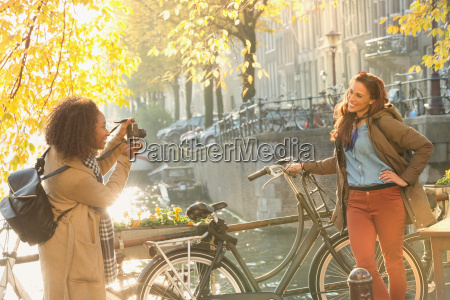 young woman photographing friend with bicycle