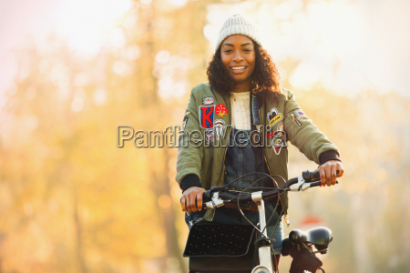 portrait smiling young woman with bicycle