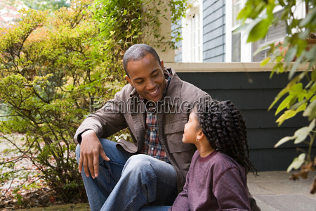 father and daughter outside house