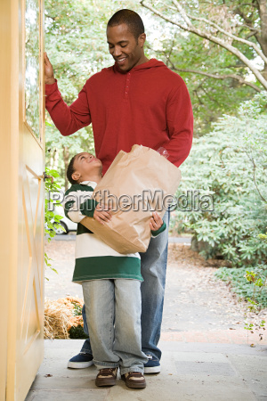 father and son with groceries