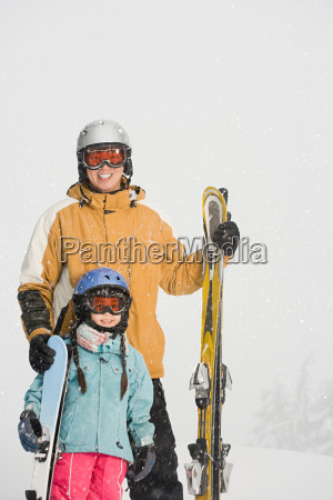 father and daughter preparing to ski