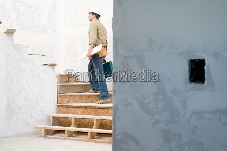 ein baumeister geht die treppe hinauf