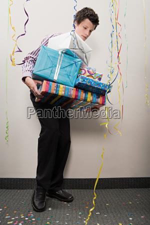 kaufmann kaempft mit haufen von geschenken