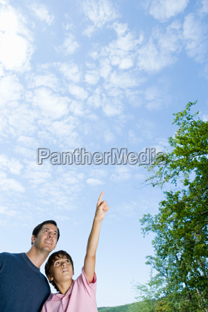 father and son looking at clouds