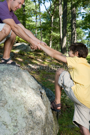 father pulling son onto rock