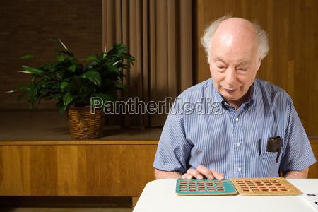 aelterer mann spielt bingo