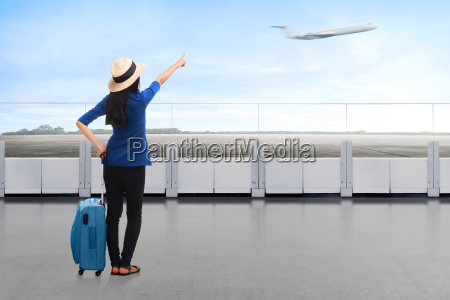 traveler asian woman carrying suitcase looking