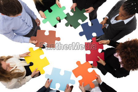 businesspeople solving jigsaw puzzle