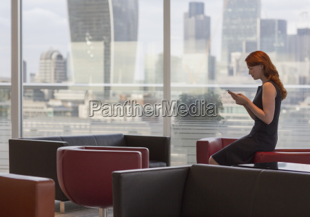 businesswoman texting with cell phone in