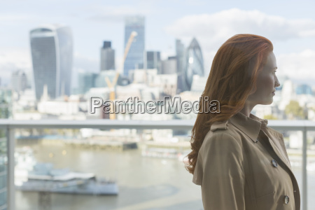 pensive businesswoman with red hair looking
