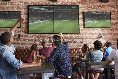 freunde beobachten spiel im sport bar