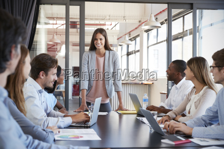 woman addressing team leans on desk