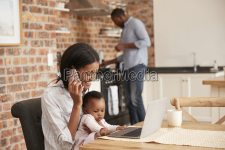 mother and baby daughter use laptop