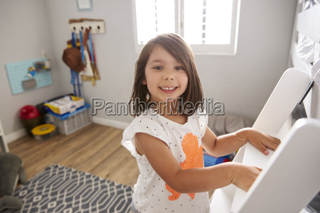 portrait of girl climbing ladder to
