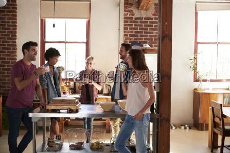 friends talking over coffee in kitchen