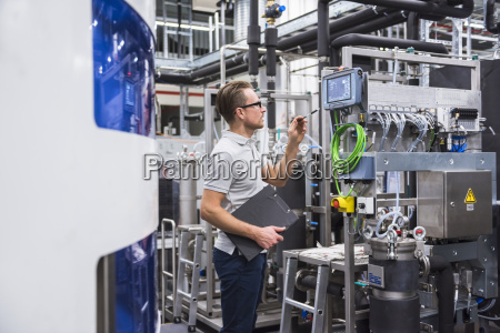 mann der bildschirm im fabrikladenboden betrachtet