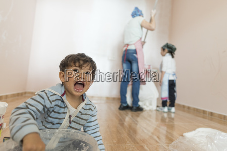 portrait of screaming little boy painting